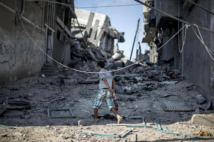 A Palestinian boy walks amid destroyed buildings in the Shejaiya district of Gaza City on July 27, 2014 as families return to find their homes ground into rubble (AFP Photo/Marco Longari)