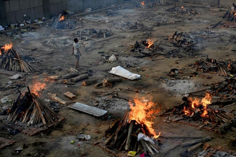 A man stands amid burning pyres of victims who lost their lives due to Covid-19 at a cremation ground in New Delhi on April 26, 2021