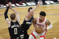 Houston Rockets' Kenyon Martin Jr., right, drives to the basket against Milwaukee Bucks' Pat Connaughton, middle, and Donte DiVincenzo, left, during the first half of an NBA basketball game Friday, May 7, 2021, in Milwaukee. (AP Photo/Aaron Gash)