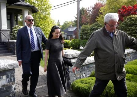 FILE PHOTO: Huawei's Financial Chief Meng Wanzhou leaves her family home flanked by private security in Vancouver, British Columbia