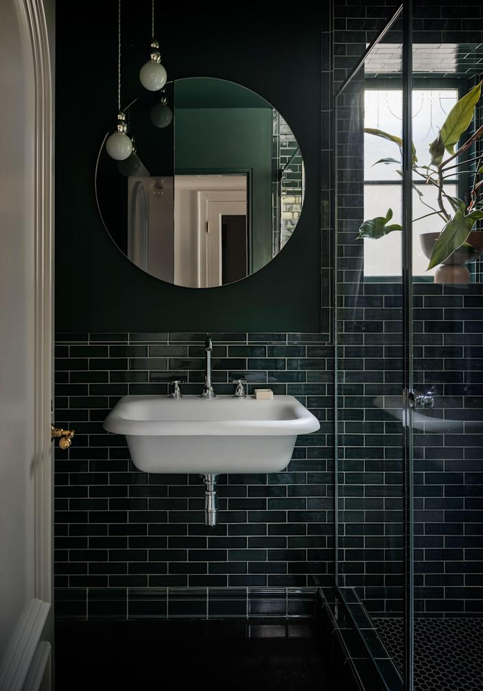 In one of the home's many bathrooms, glossy hunter green tiles pair perfectly with a matching wall color.