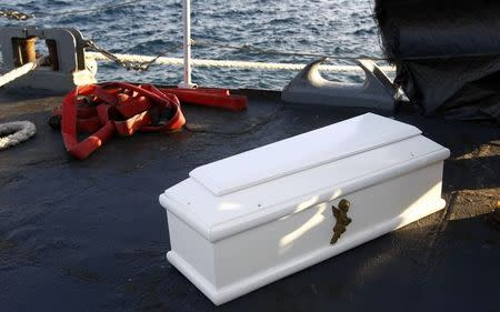 A coffin containing the body of a migrant who died is seen aboard a navy ship at the Sicilian harbour of Augusta