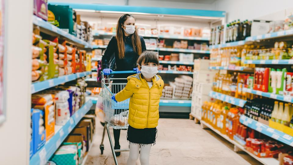 mother and daughter wearing masks and gloves and shopping.