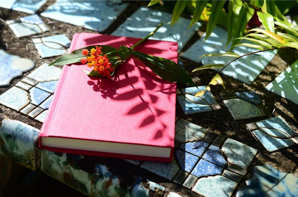 A journal sitting on tile with a flower on top.