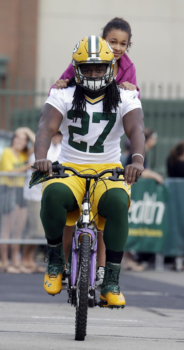 Green Bay Packers' Eddie Lacy rides a bike to NFL football training camp on Saturday, July 26, 2014, in Green Bay, Wis. (AP Photo/Morry Gash)