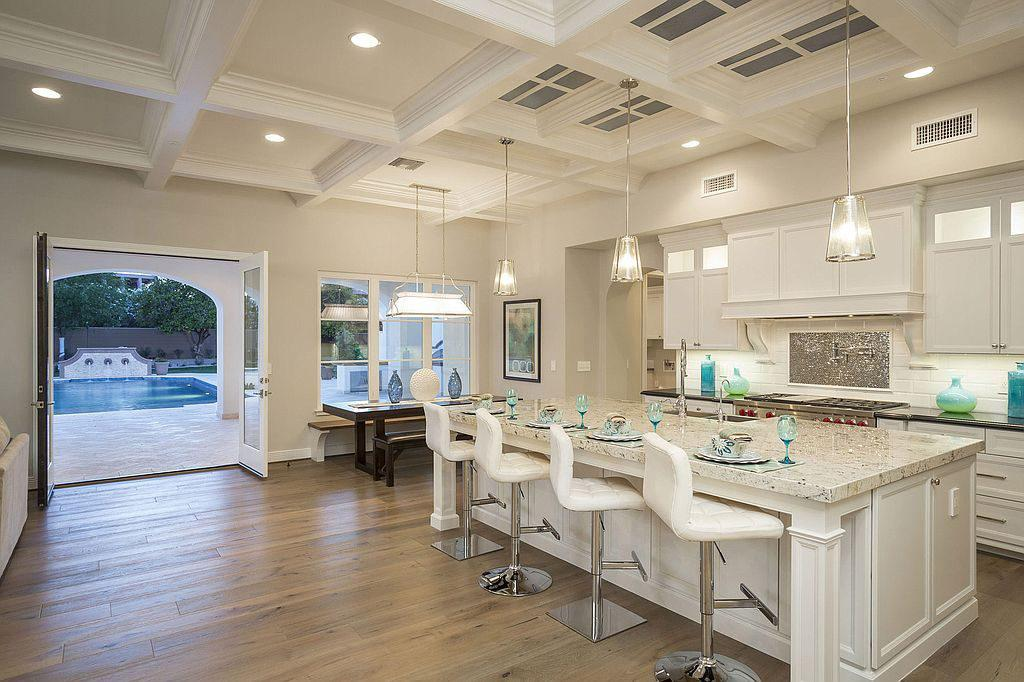 <p>The kitchen, with a marble island and French doors leading out to the pool area, offers an inviting space for cooking with family and friends. </p>