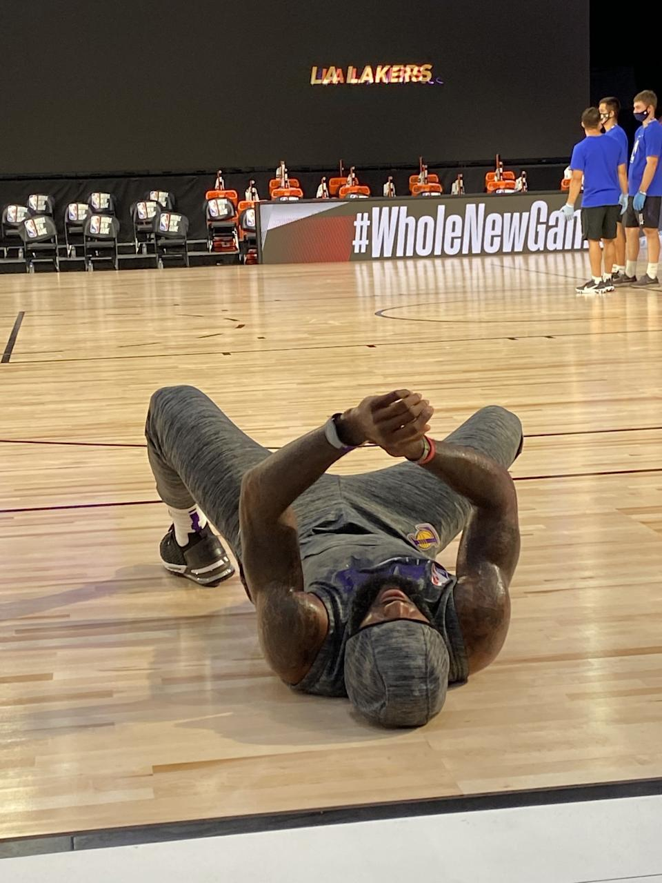 Lakers star LeBron James, while wearing his MagicBand, stretches before a game in the NBA bubble in Orlando.