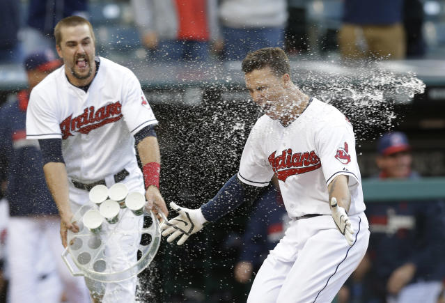 Cleveland Indians' Lonnie Chisenhall, left, throws cups of water on Zach Walters after Walters hit a game-winning solo home run in the ninth inning of the first baseball game of a doubleheader against the Arizona Diamondbacks, Wednesday, Aug. 13, 2014, in Cleveland. The Indians defeated the Diamondbacks 3-2. (AP Photo/Tony Dejak)