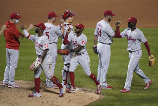 Philadelphia Phillies center fielder Roman Quinn (24) celebrates with teammates after closing the ninth inning of a baseball game against the New York Mets, Friday, Sept. 4, 2020, in New York. (AP Photo/John Minchillo)