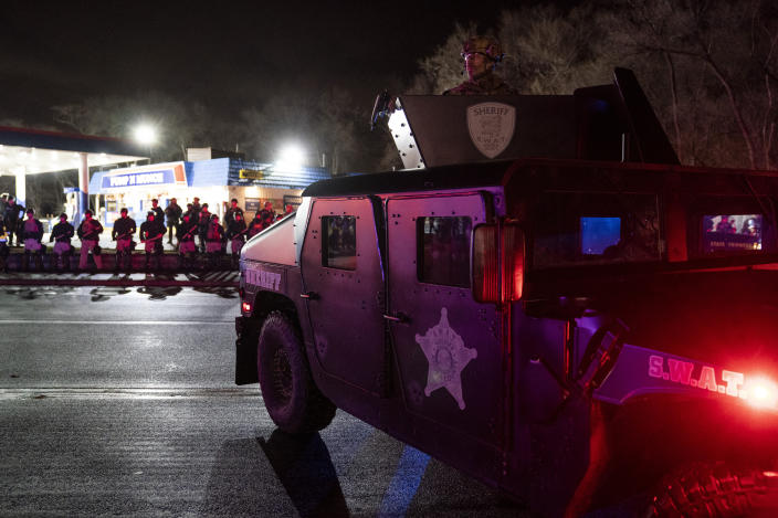 Authorities advance into a gas station after pursuing demonstrators for violating curfew and issuing orders to disperse during a protest against the police shooting of Daunte Wright, late Monday, April 12, 2021, in Brooklyn Center, Minn. (AP Photo/John Minchillo)