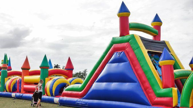A row of colorful bounce houses are located on a grassy field at a public park in suburban Palm Beach County, FL.