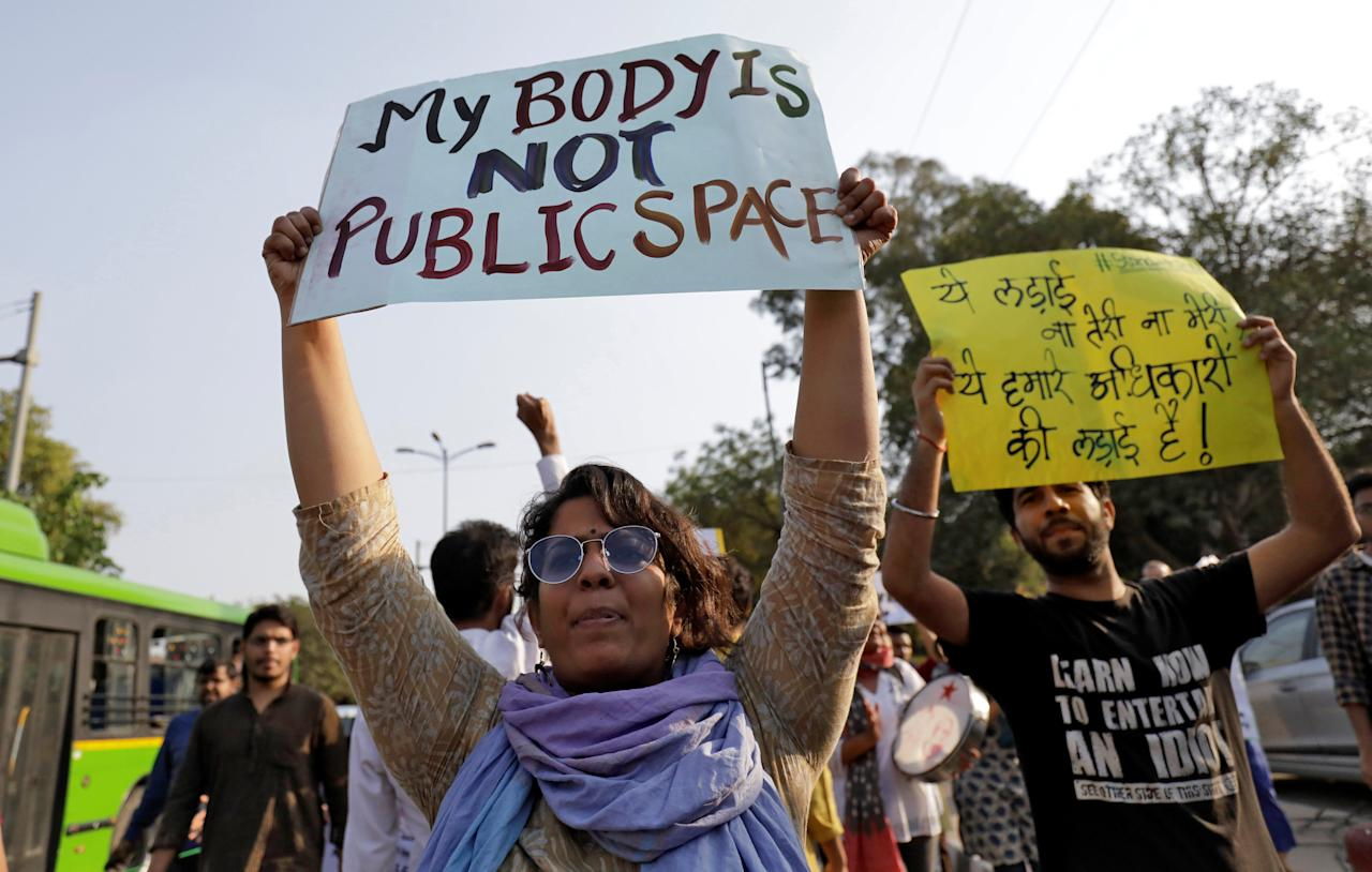 """Students and teachers of Jawaharlal Nehru University (JNU) hold placards as they participate in a protest march demanding suspension of a professor accused of sexual harassment, in New Delhi, India, March 23, 2018. The placard on the right reads: """"This fight is neither your nor mine, it is for our rights"""". REUTERS/Saumya Khandelwal"""