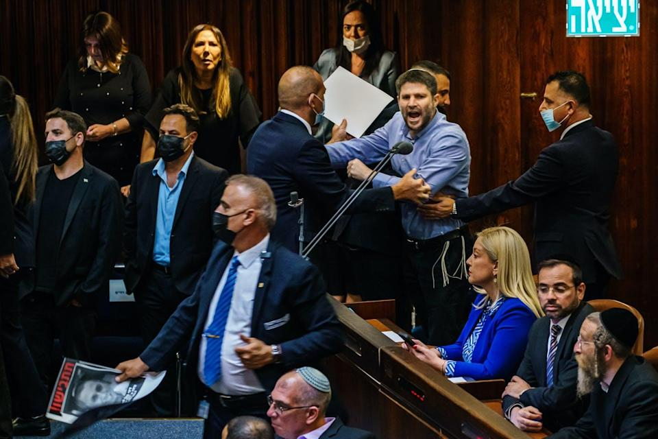 A shouting man is pushed out of legislative chamber