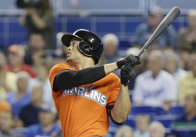 Miami Marlins' Giancarlo Stanton watches the ball after hitting a two-run home run, scoring Derek Dietrich, during the first inning of a baseball game against the Los Angeles Dodgers, Sunday, May 4, 2014, in Miami. (AP Photo/Wilfredo Lee)