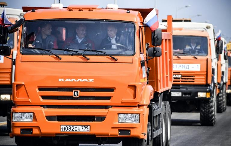 Russian President Vladimir Putin (R) drives a construction truck across the new bridge over the Kerch Strait linking mainland Russia to Moscow-annexed Crimea during the opening ceremony on May 15, 2018