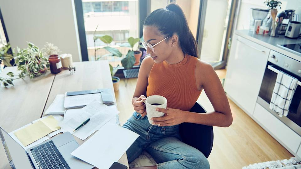 A woman cradles a cup of coffee as she works on her taxes.