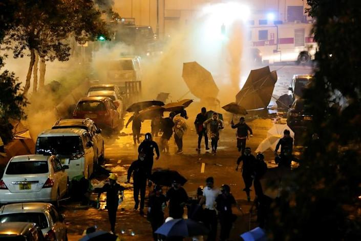 Anti-government demonstrators run from a water cannon during clashes with police near the Hong Kong Polytechnic University (PolyU) in Hong Kong