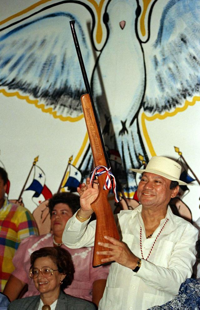 <p>Gen. Manuel Noriega holds a rifle bearing his name, given to him by a supporter during a pro-government rally, in Santiago, Panama, Oct. 5, 1989. (AP Photo/Matias Recart) </p>