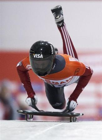 Fairbairn of Canada jumps on his sled in the first run during the men's skeleton race at the FIBT Bobsleigh and Skeleton World Cup competition in Calgary.