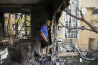 A member of Sror family inspect the damage of their apartment after being hit by a rocket fired from the Gaza Strip over night, in Petah Tikva, central Israel, Thursday, May 13, 2021. (AP Photo/Oded Balilty)