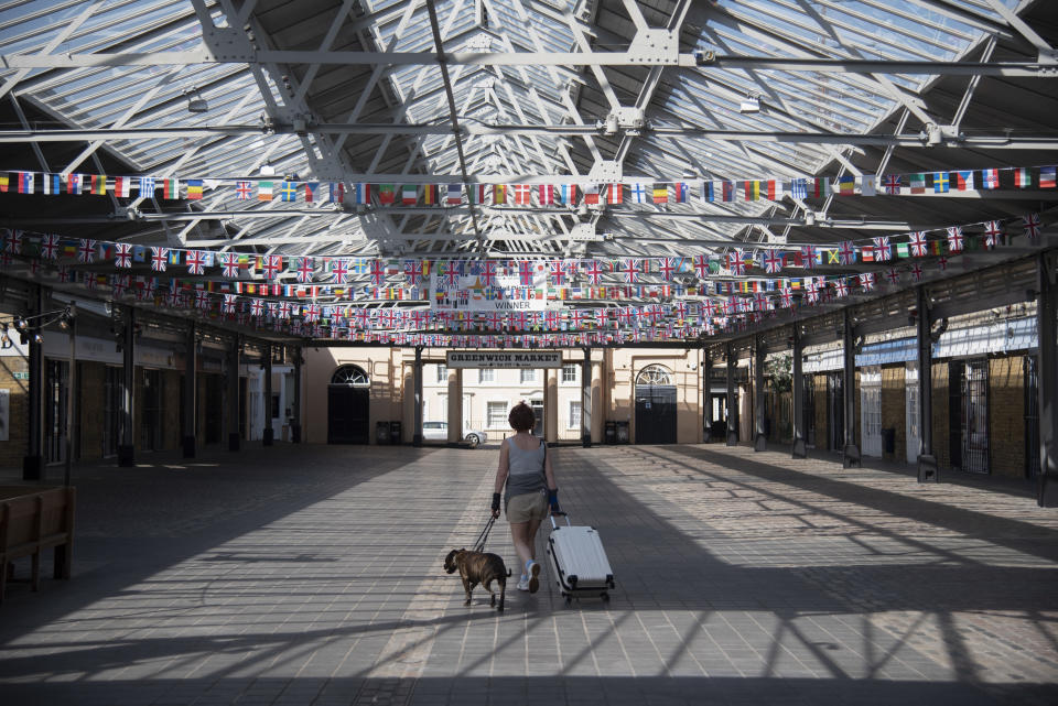 """A women walks through an empty Greenwich Market with a dog and suitcase on 15th April 2020 in Greenwich, London, United Kingdom. Chancellor of the Exchequer, Rishi Sunak has said the Office for Budget Responsibility (OBR), the UK's tax and spending watchdog suggests the coronavirus crisis will have """"serious implications"""" for the UK economy, warning the pandemic could see the economy shrink by a record 35% by June, increasing unemployment by over 2 million and sending the budget deficit to its highest since World War II. (photo by Claire Doherty/In Pictures via Getty Images)"""