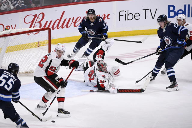 Ottawa Senators' goaltender Craig Anderson (41) slides out of his crease as Winnipeg Jets' Mark Scheifele (55) tries to shoot the puck past Nikita Zaitsev (22) during first period NHL action in Winnipeg on Saturday Feb. 8, 2020. (Fred Greenslade/The Canadian Press via AP)