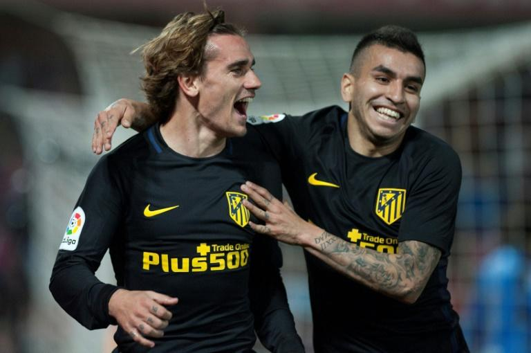 Atletico Madrid's Antoine Griezmann (L) celebrates with teammate Angel Correa after scoring during their Spanish La Liga match against Granada, at Nuevo Los Carmenes stadium in Granada, on March 11, 2017