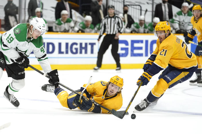 Nashville Predators center Rem Pitlick (16) reaches for the puck between teammate Nick Cousins (21) and Dallas Stars center Rhett Gardner (49) in the second period of an NHL hockey game Sunday, April 11, 2021, in Nashville, Tenn. (AP Photo/Mark Humphrey)