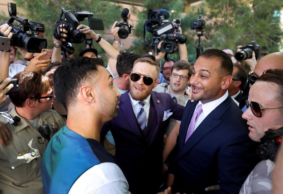 Boxer Paulie Malignaggi (L) talks with UFC lightweight champion Conor McGregor (C) of Ireland and McGregor's manager Audie Attar at Toshiba Plaza in Las Vegas, Nevada U.S. on August 22, 2017. (Reuters)