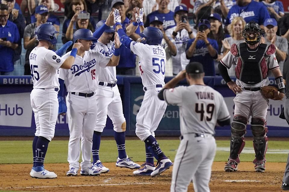The Dodgers' Mookie Betts (50) is congratulated by teammates after hitting a seventh-inning grand slam July 10, 2021.