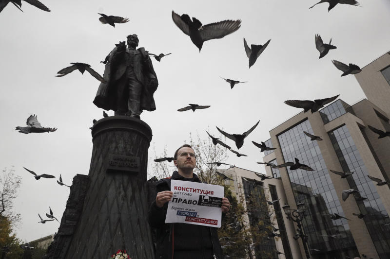 """An opposition activist holds a poster reading """"The authorities trample on the Constitution/ Bring freedom and Constitution back to people!"""" during a protest in the center of Moscow, Russia, Saturday, Aug. 17, 2019. People rallied Saturday against the exclusion of some city council candidates from Moscow's upcoming election. (AP Photo)"""