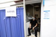 Medical staff member collects a swab from a man for nucleic acid test at China-Japan Friendship Hospital in Beijing