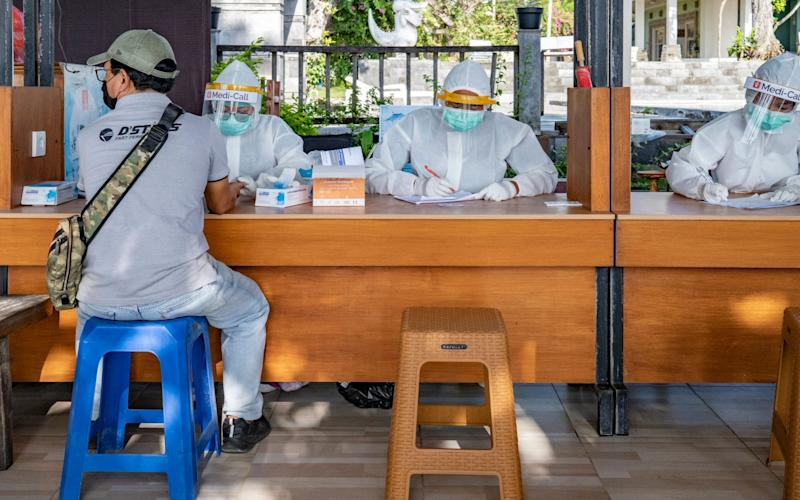 Healthcare workers wearing protective suits conduct a rapid test for coronavirus in Denpasar, Bali - Shutterstock