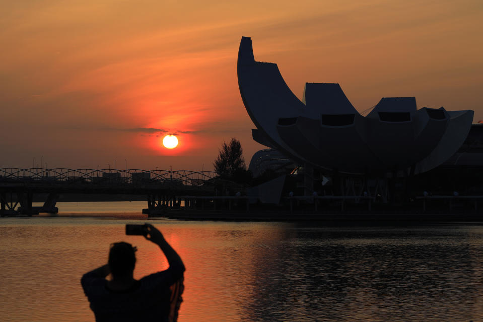 A woman takes a photo as the sun rises behind the ArtScience Museum at Marina Bay on February 15, 2021 in Singapore.  (Photo by Suhaimi Abdullah/NurPhoto via Getty Images)