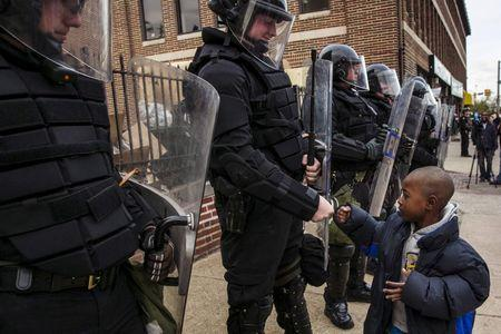 File photo of a young boy greeting police officers in riot gear during a march in Baltimore, Maryland