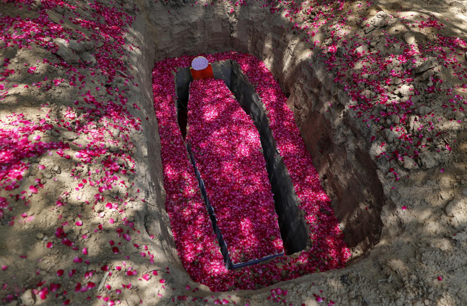 Rose petals are spread around the grave and coffin of Father Rolfie D'Souza's who died of COVID-19, at a cemetery in Prayagraj, India, Saturday, May 15, 2021. India's Prime Minister Narendra Modi on Friday warned people to take extra precautions as the virus was spreading fast in rural areas. (AP Photo/Rajesh Kumar Singh)