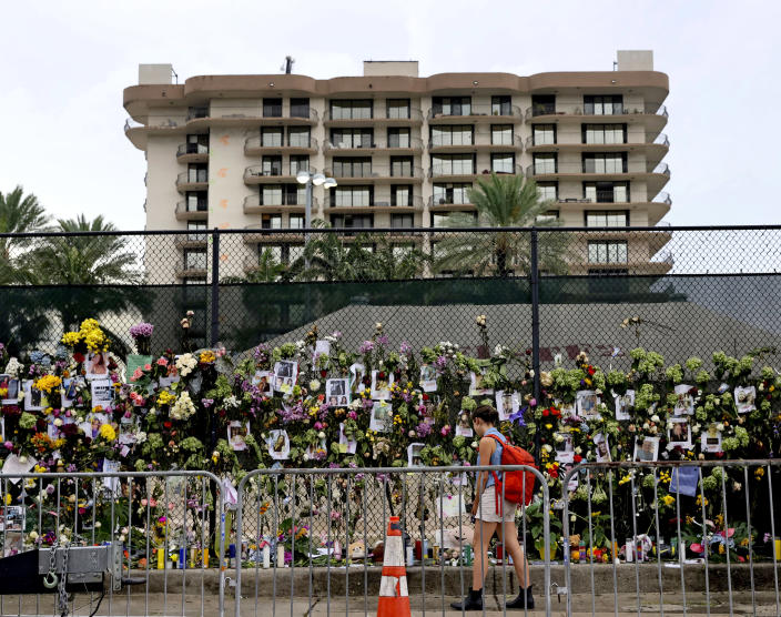 Image: A woman visits the memorial wall full of photos of the missing and messages of love, support and prayers at Harding Avenue and 86th Street as search and rescue personnel continue to look for survivors in the rubble of the Champlain Towers (David Santiago / Miami Herald via AP)