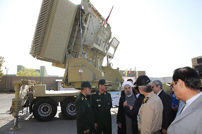 A handout picture provided by the office of Iran's President Hassan Rouhani on August 21, 2016 shows him (3rd-R) and then defence minister Hossein Dehghan (2nd-L) standing next to the new Bavar 373 missile defence system in Tehran
