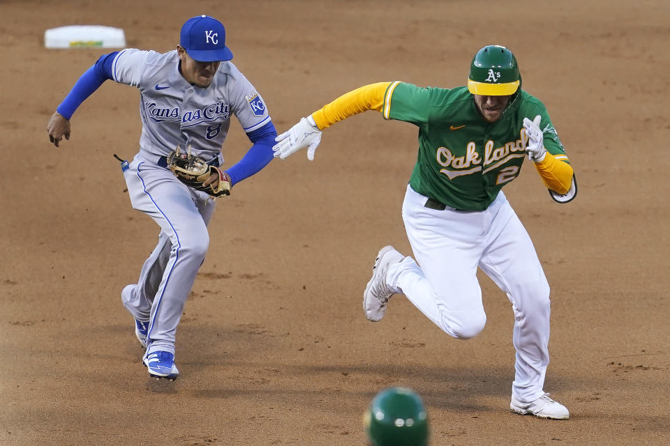 Oakland Athletics' Stephen Piscotty, right, is chased by Kansas City Royals shortstop Nicky Lopez before being tagged out while trying to advance after singling during the fifth inning of a baseball game in Oakland, Calif., Thursday, June 10, 2021. (AP Photo/Jeff Chiu)