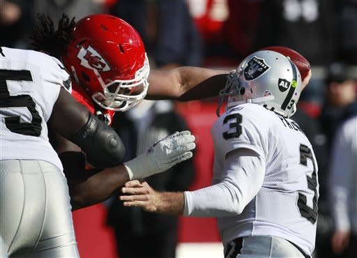 Oakland Raiders quarterback Carson Palmer (3) is pressured by Kansas City Chiefs defensive end Tyson Jackson (94) during the first half of an NFL football game at Arrowhead Stadium in Kansas City, Mo., Saturday, Dec. 24, 2011. (AP Photo/Orlin Wagner)