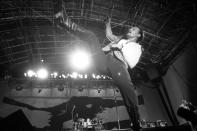 "FOXBOROUGH, MA - SEPTEMBER 22: Lead vocalist Bono of U2 kicks in the air as the band performs at Sullivan Stadium in Foxborough, MA on Sep. 22, 1987 during their tour supporting ""The Joshua Tree."" (Photo by Suzanne Kreiter/The Boston Globe via Getty Images)"