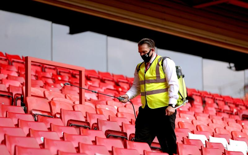 A steward disinfects the stands after the attending fans leave the grounds at the end of the Sky Bet League One match at The Valley, London - Steven Paston/PA