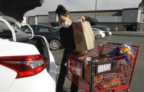 FILE - In this July 1, 2020 file photo, Instacart worker Saori Okawa loads groceries into her car for home delivery in San Leandro, Calif. A judge has struck down California's ballot measure that exempted Uber and other companies from a state law requiring their drivers to be classified as employees eligible for benefits and job protections, Friday, Aug. 20, 2021. (AP Photo/Ben Margot, File)