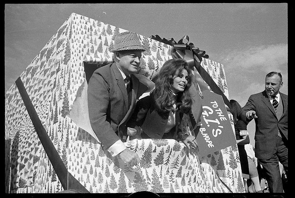 <p>Wearing a suit and a tweed fedora, Bob Hope busted through a giant Christmas present with actress Raquel Welch. The comedian was about to embark on a holiday tour of military bases. </p>