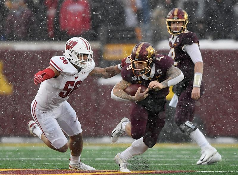 MINNEAPOLIS, MINNESOTA - NOVEMBER 30: Zack Baun #56 of the Wisconsin Badgers tackles Shannon Brooks #4 of the Minnesota Golden Gophers during the second quarter of the game at TCF Bank Stadium on November 30, 2019 in Minneapolis, Minnesota. (Photo by Hannah Foslien/Getty Images)