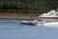 In this handout photo taken from video released by Russian Emergency Situations Ministry press service, a Russian Emergency Ministry's Beriev multipurpose amphibious aircraft Be-200 takes-off to drop water during extinguishing a forest fire in the republic of Sakha also knows as Yakutia, Russia Far East, Sunday, July 18, 2021. Russia has been plagued by widespread forest fires, blamed on unusually high temperatures and the neglect of fire safety rules, with Sakha-Yakutia in northeastern Siberia being the worst affected region lately. Local emergency officials said 187 fires raged in the region on Sunday, and the total areas engulfed by blazes have grown by 100,000 hectares (about 247,000 acres) in the past 24 hours. (Russian Emergency Situations Ministry press service via AP)
