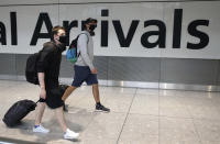 Passengers arrive at Heathrow Airport, in London, Sunday July 26, 2020. The British government has announced 14-day quarantine restrictions from Sunday, for people arriving into England from certain countries including Spain, after Covid-19 second wave fears saw the European country struck off the UK's safe list. (Andrew Matthews/PA via AP)