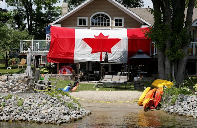 A man hangs a Canadian flag on the deck of his cottage in Rideau Ferry, Ontario, Canda July 1, 2016. REUTERS/Gary Cameron