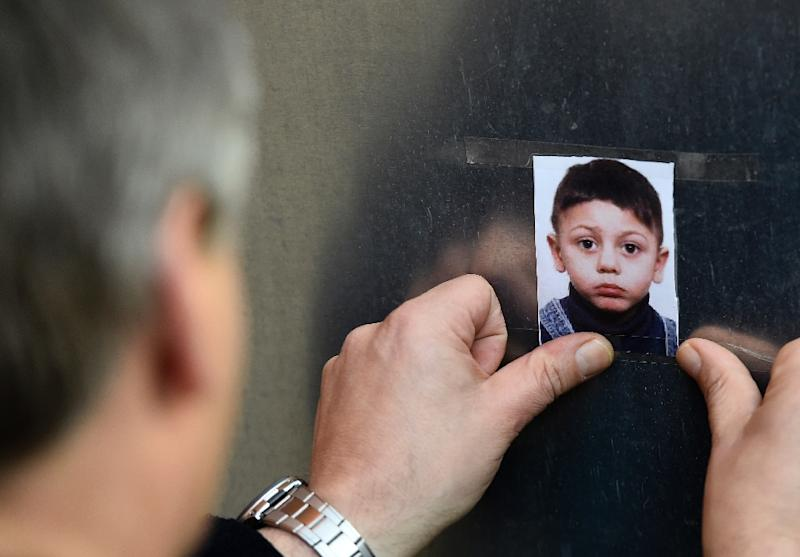 A man sticks a photo of missing Bosnian boy Mohamed on a wall at the State Office of Health and Social Affairs in Berlin on October 29, 2015 (AFP Photo/Tobias Schwarz)