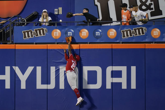 Philadelphia Phillies' Andrew McCutchen leaps at the wall to catch a ball hit by New York Mets' Albert Almora Jr. for an out during the second inning of the second baseball game of a doubleheader Friday, June 25, 2021, in New York. (AP Photo/Frank Franklin II)